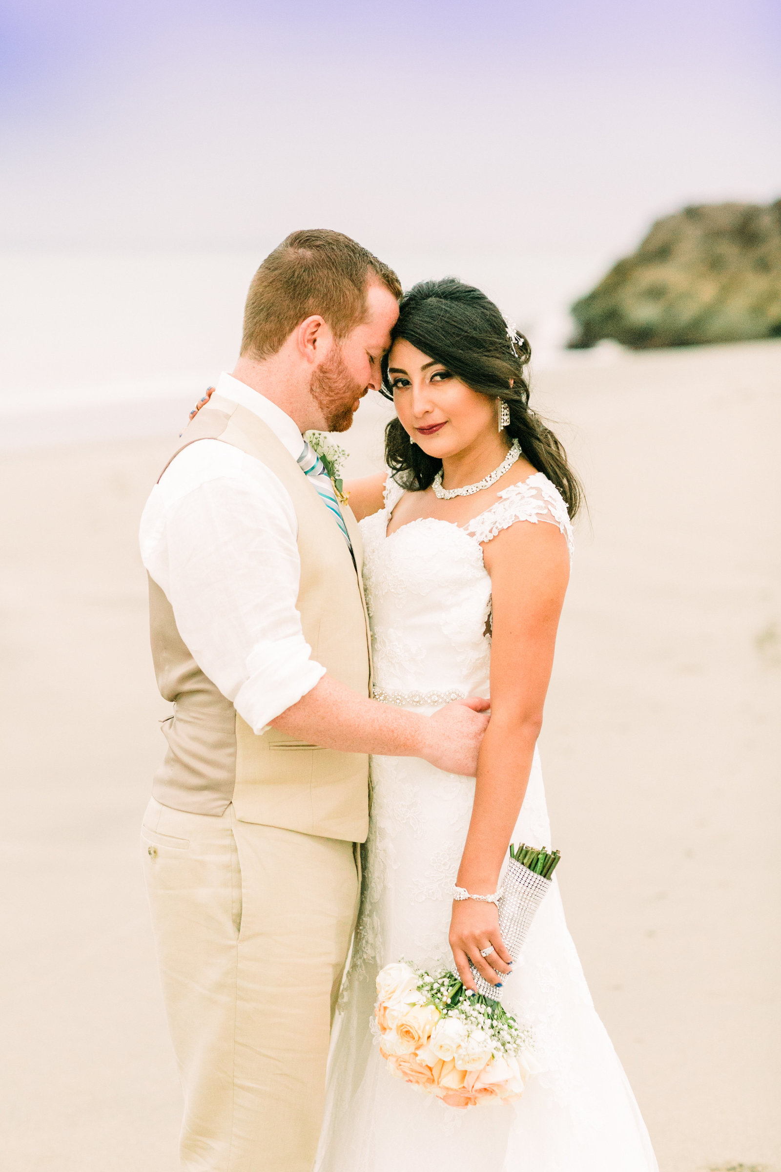 Bride and Groom, Alex and Cristina, pose on the beach of Ecuador after their wedding ceremony.