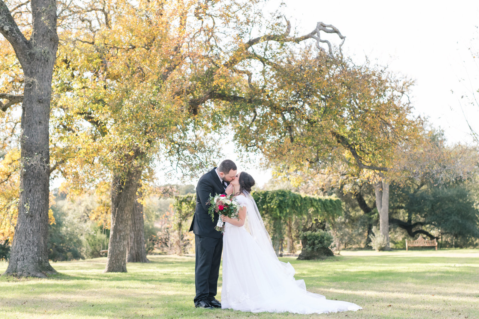 Bride and groom kiss at Pecan Springs Ranch winter wedding