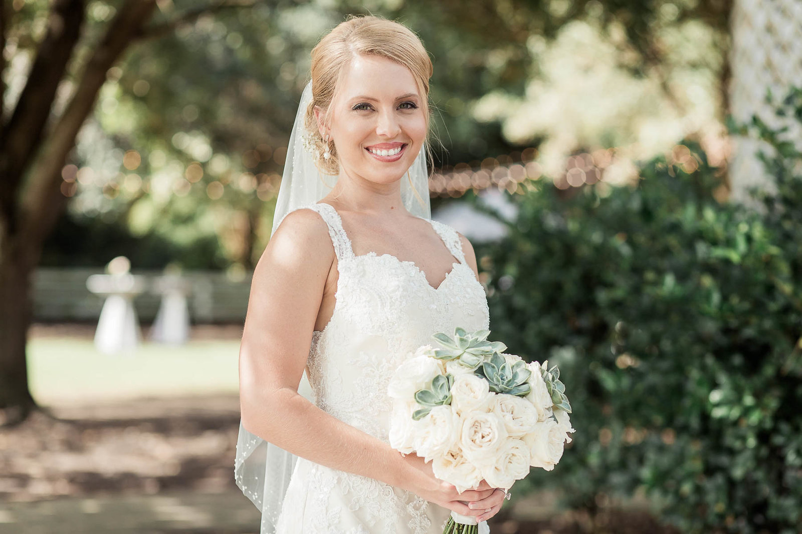 Bride stands underneath trees, Alhambra Hall, Mt Pleasant, South Carolina
