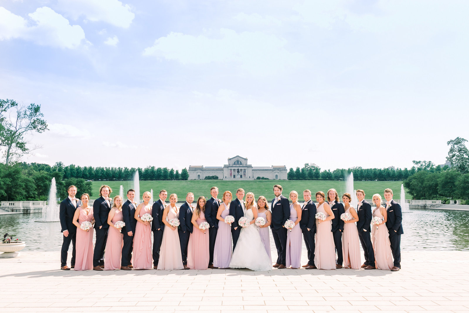 Molly and Marcus's wedding party of 22 people pose in front of the St. Louis Art Museum and Grand Basin with a beautiful clear blue sky.