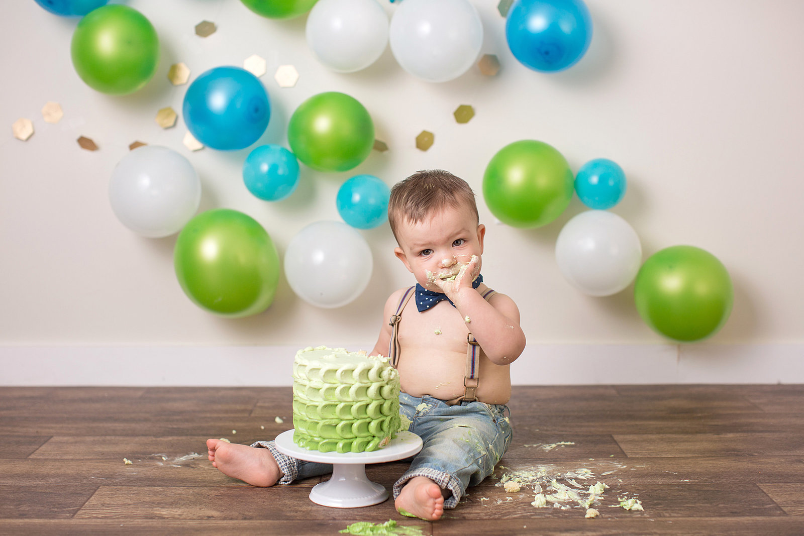 baby eats green frosting cake