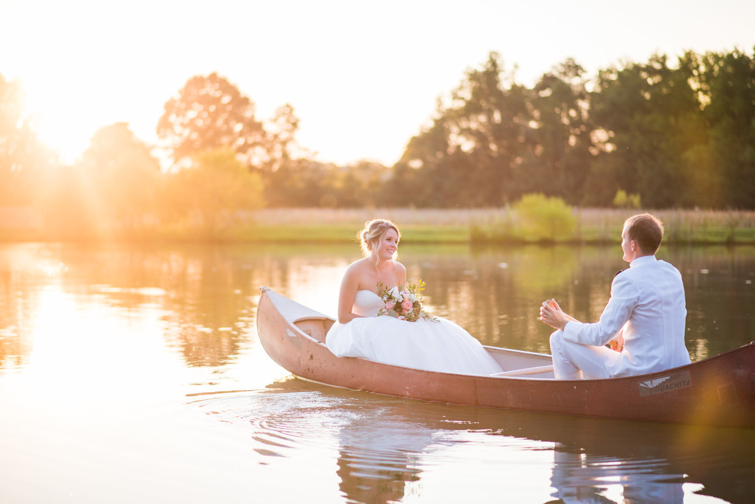 romantic image of couple in canoe during sunset at wedding