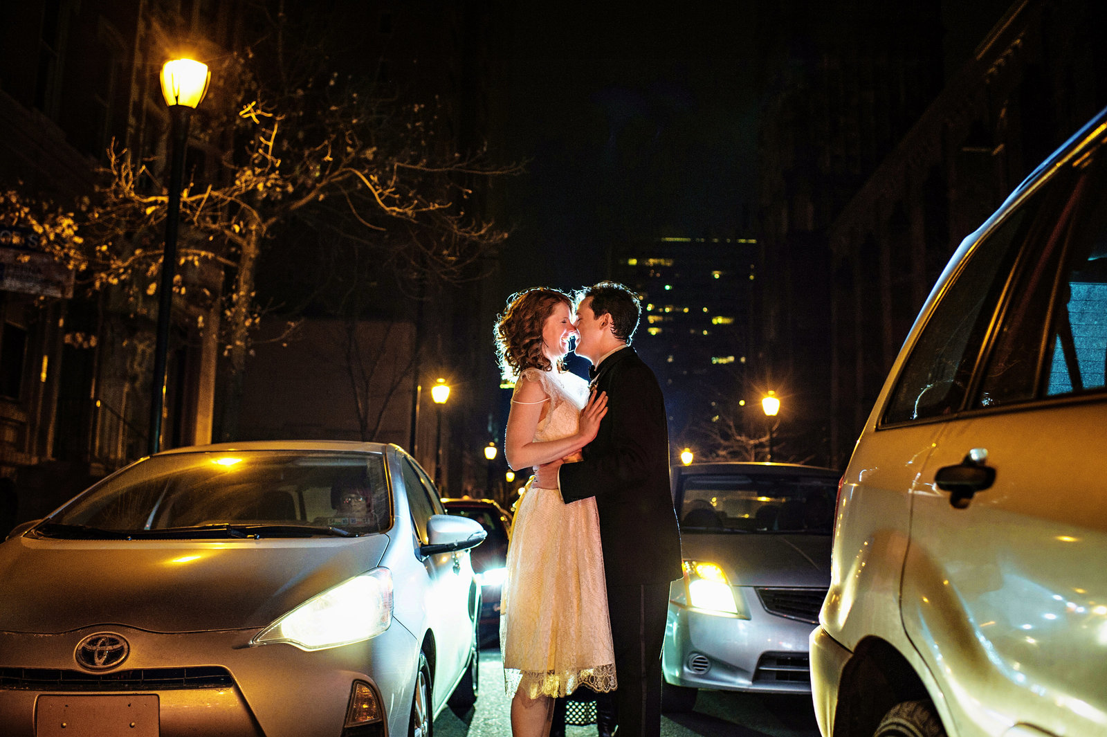 A wedding couple kiss in the middle of Walnut Street outside of Stotesbury Mansion.