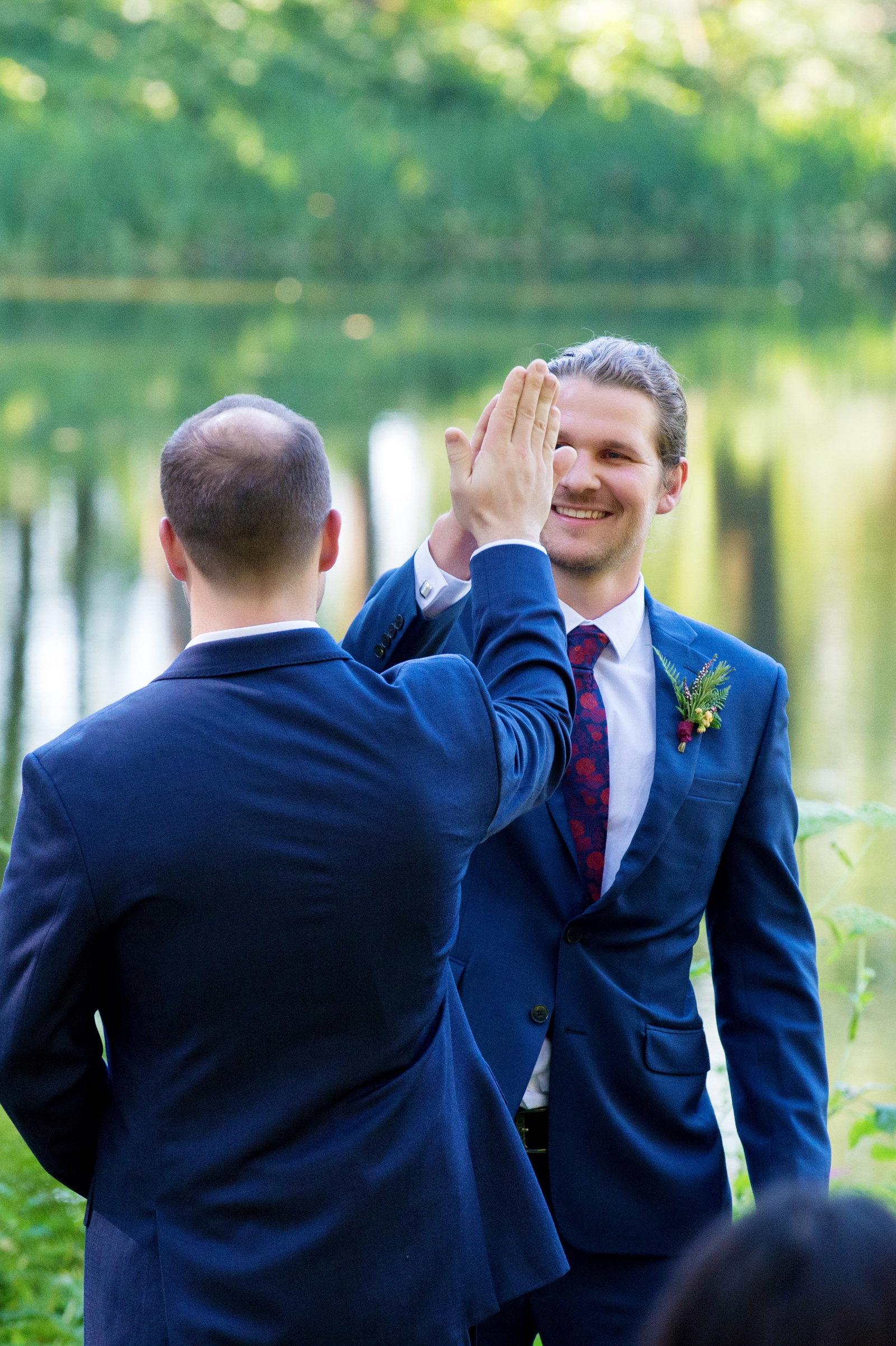 groomsman gives groom a high five at front of ceremony
