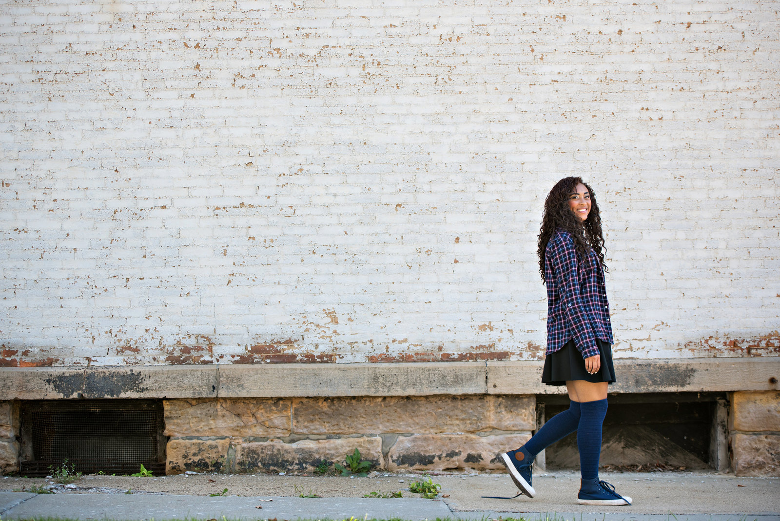 Senior Portrait of a girl walking along a bricked building.