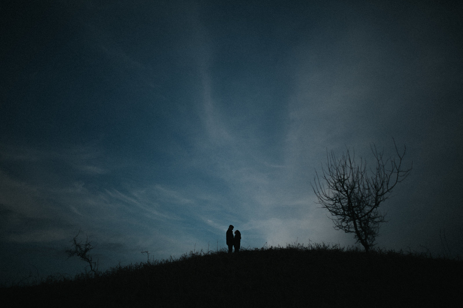 Engaged couple silhouetted against dramatic sunset by Lake District Wedding Photographer Jono Symonds