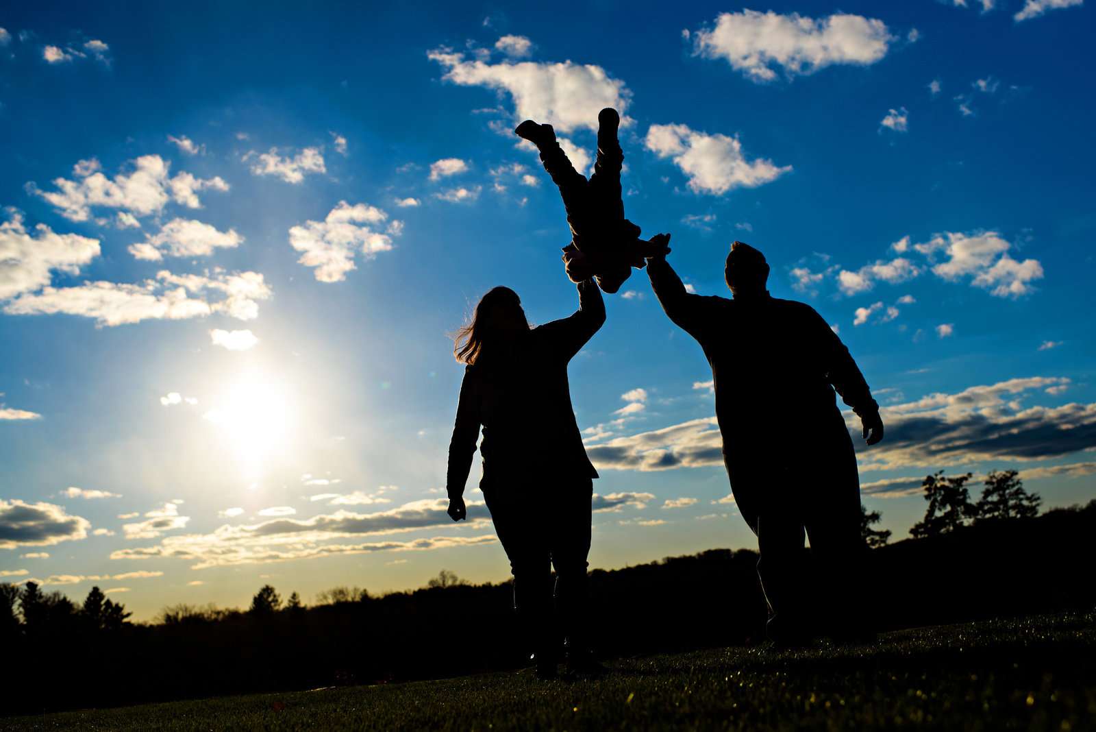 A silhouette of a family swinging their baby up in the air.