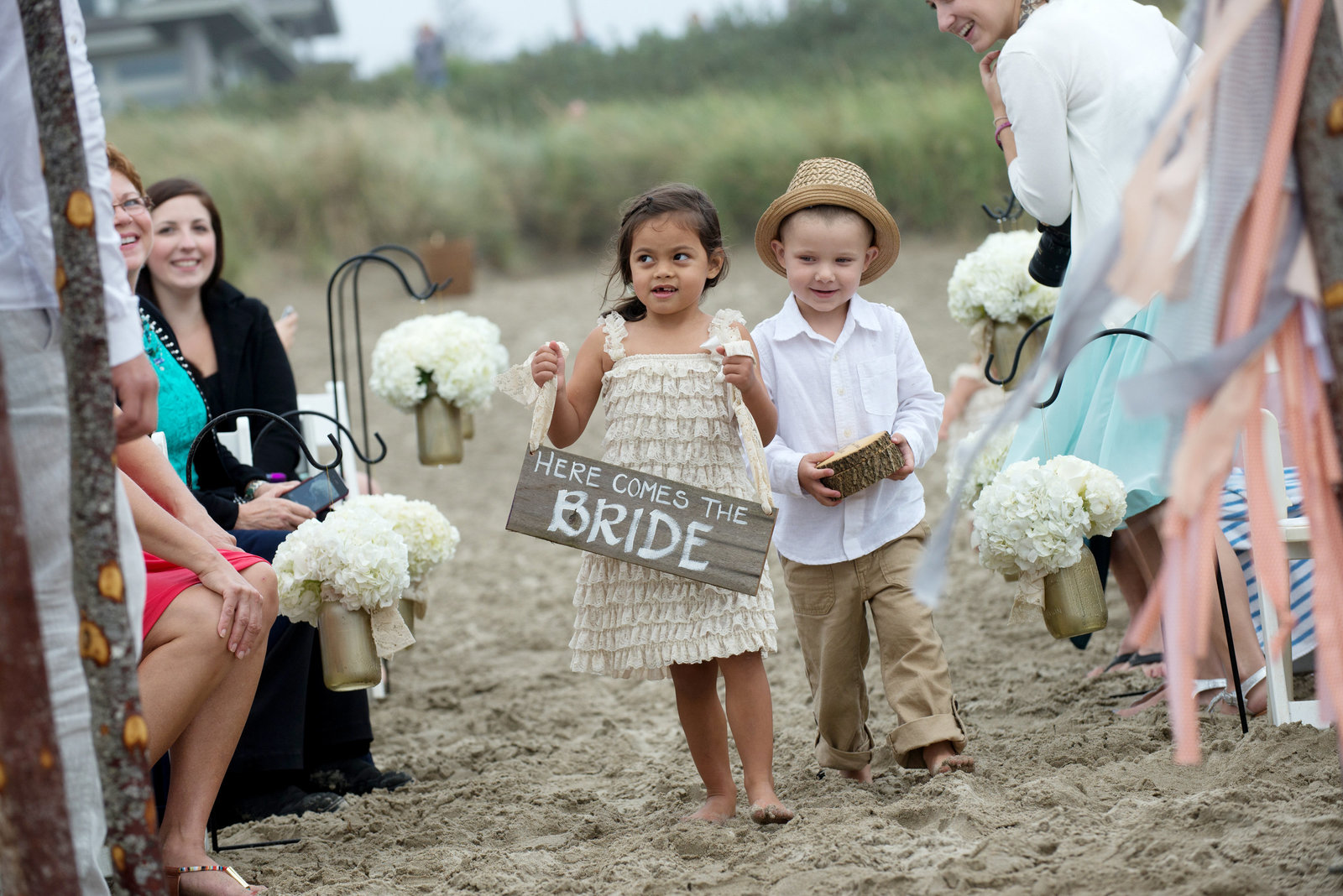 ring bearer walks sign down wedding aisle