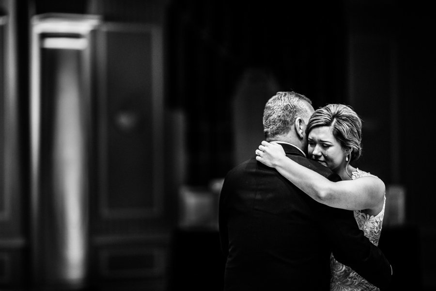 a daughter is emotional at her wedding while dancing with her father