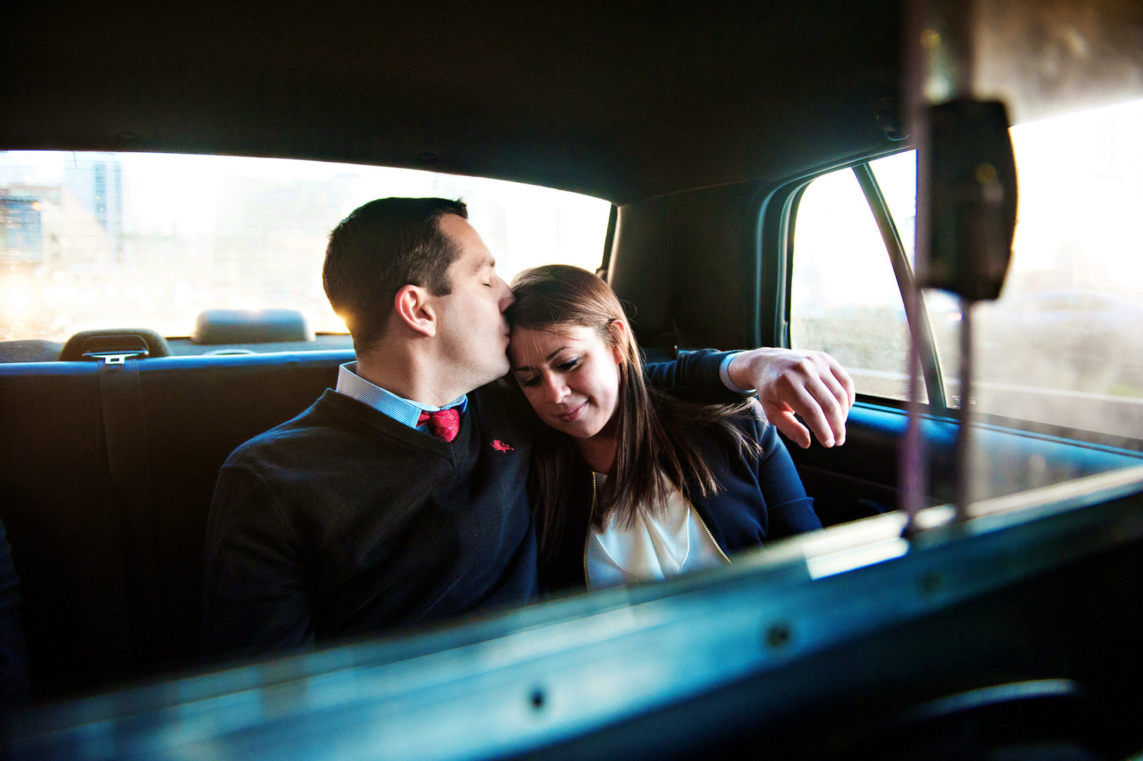 A couple share a quiet moment while riding in the back of a NYC Taxi on the way to the next location.