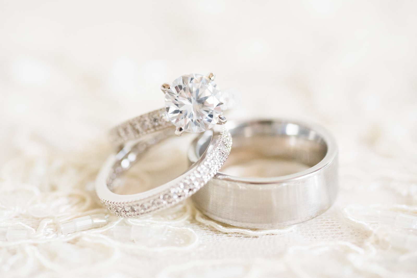 Engagement and wedding rings on lace wedding dress photo