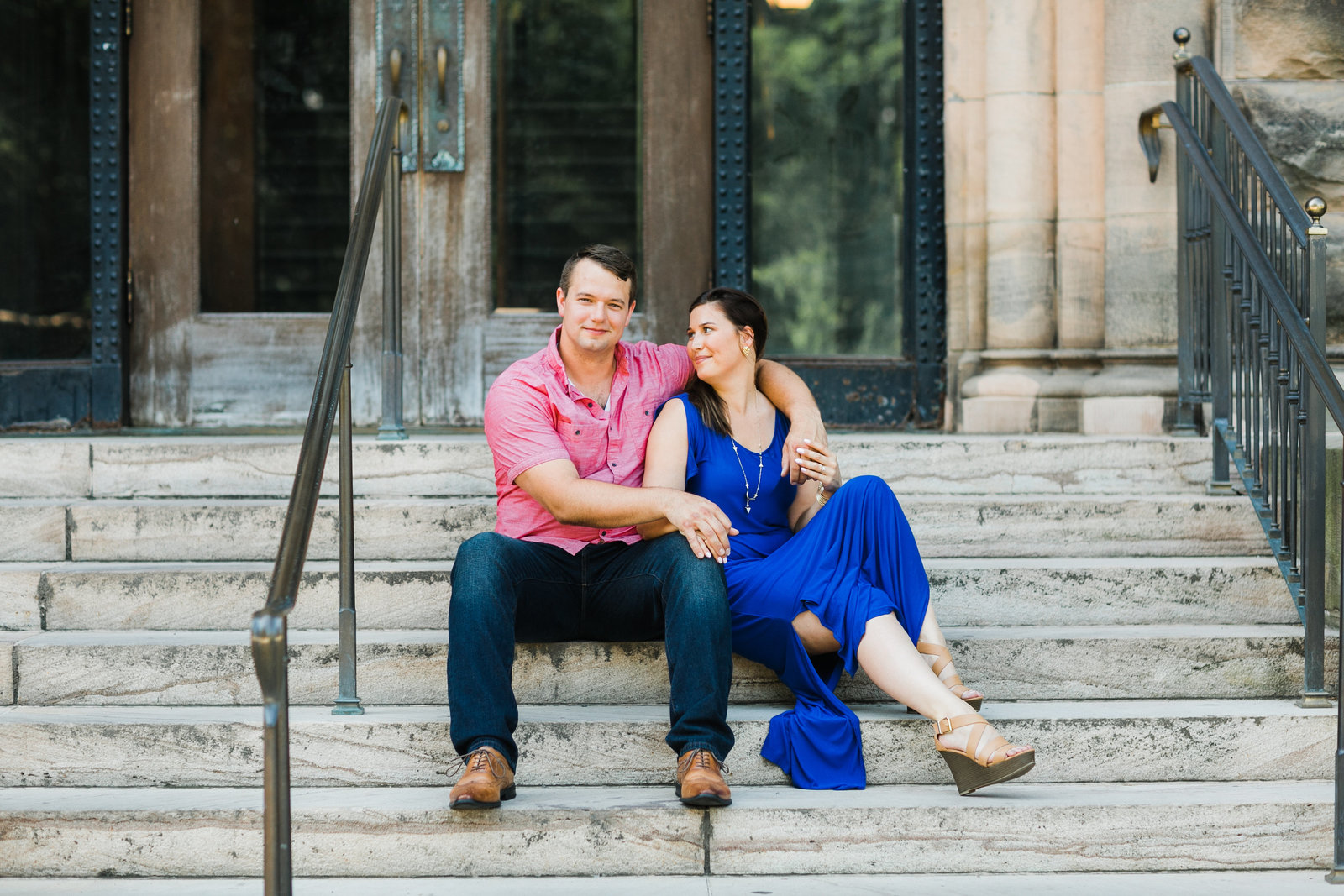 Engagement photo of Corrie and Neal sitting on building stairs at the University of Illinois.