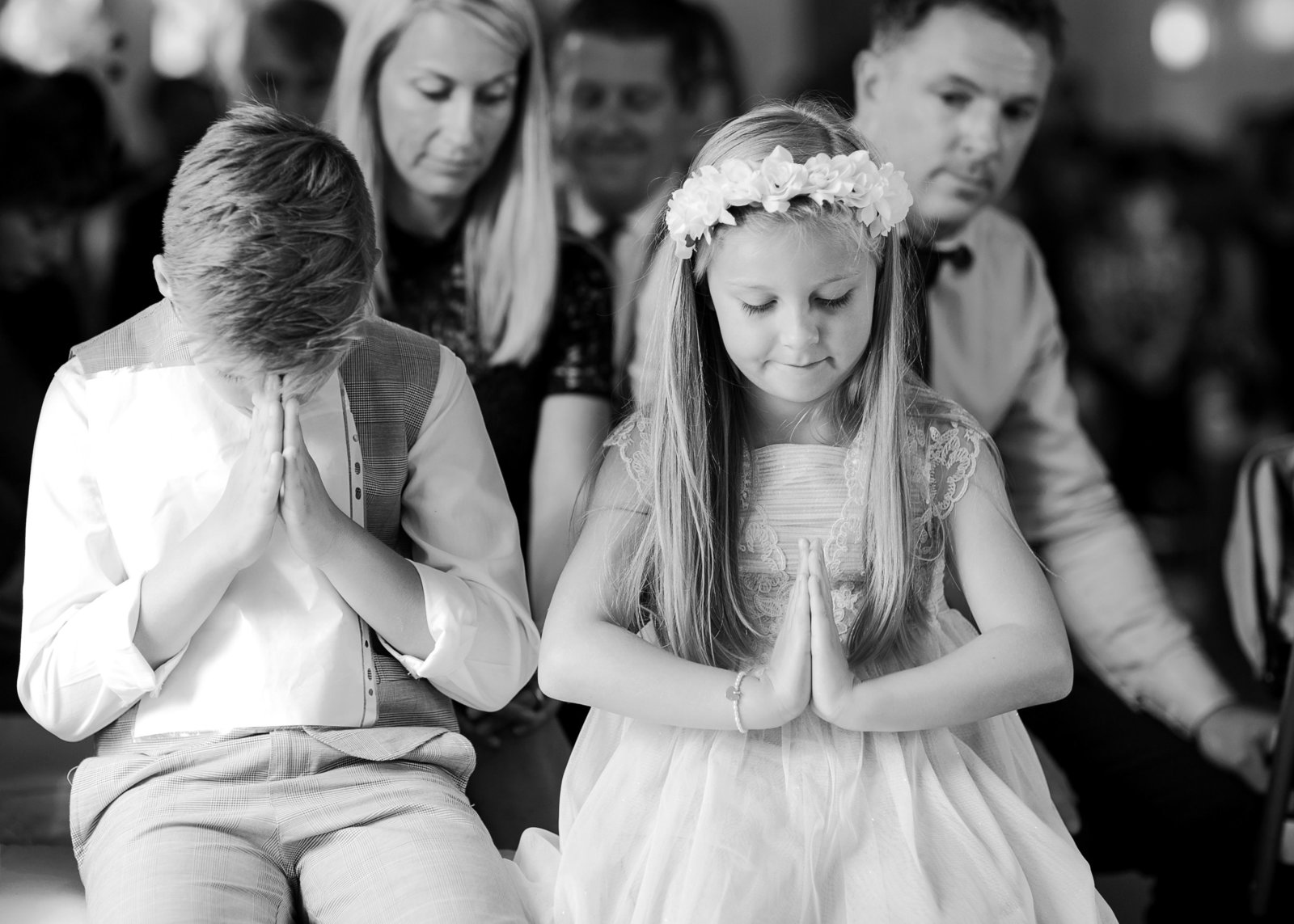 Page boy and flowergirl pray during blessing at this Southend Barns Wedding ceremony