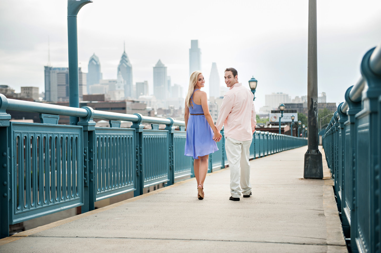 A couple walk on the ben franklin bridge with the philadelphia skyline behind them.
