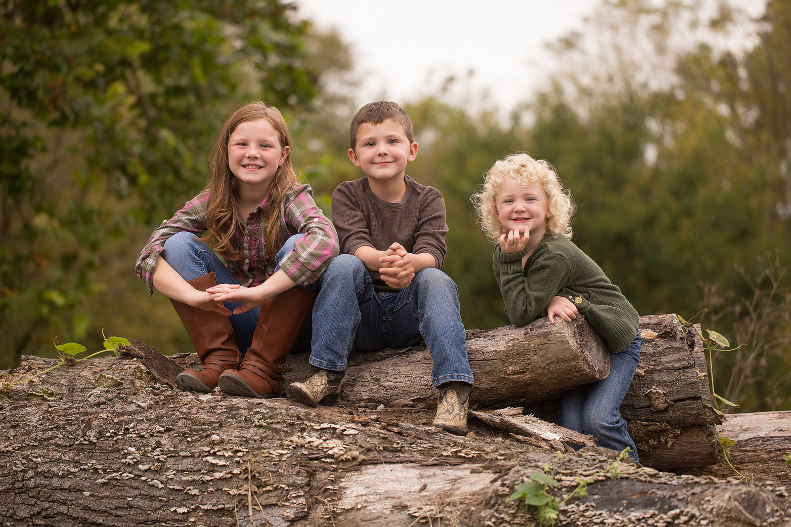 Children pose for photo sitting on pile of logs