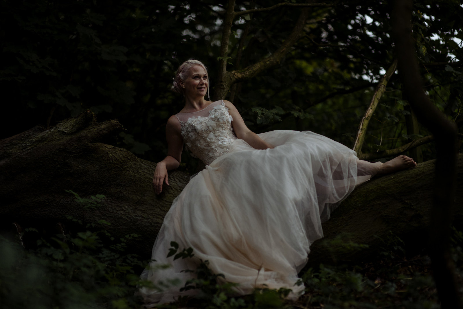 Bride in pale pink dress in woodland at Lineham Farm, Leeds. Yorkshire fine art wedding photographer