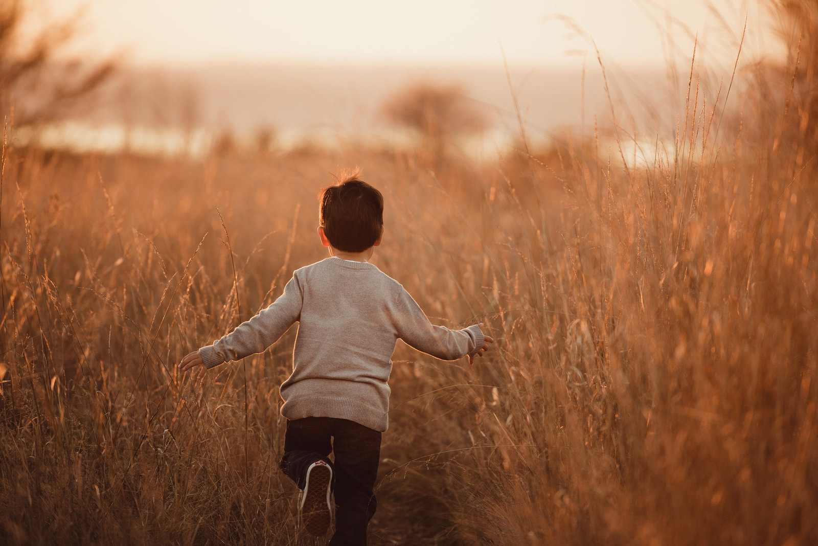 little boy running through a field in Seattle