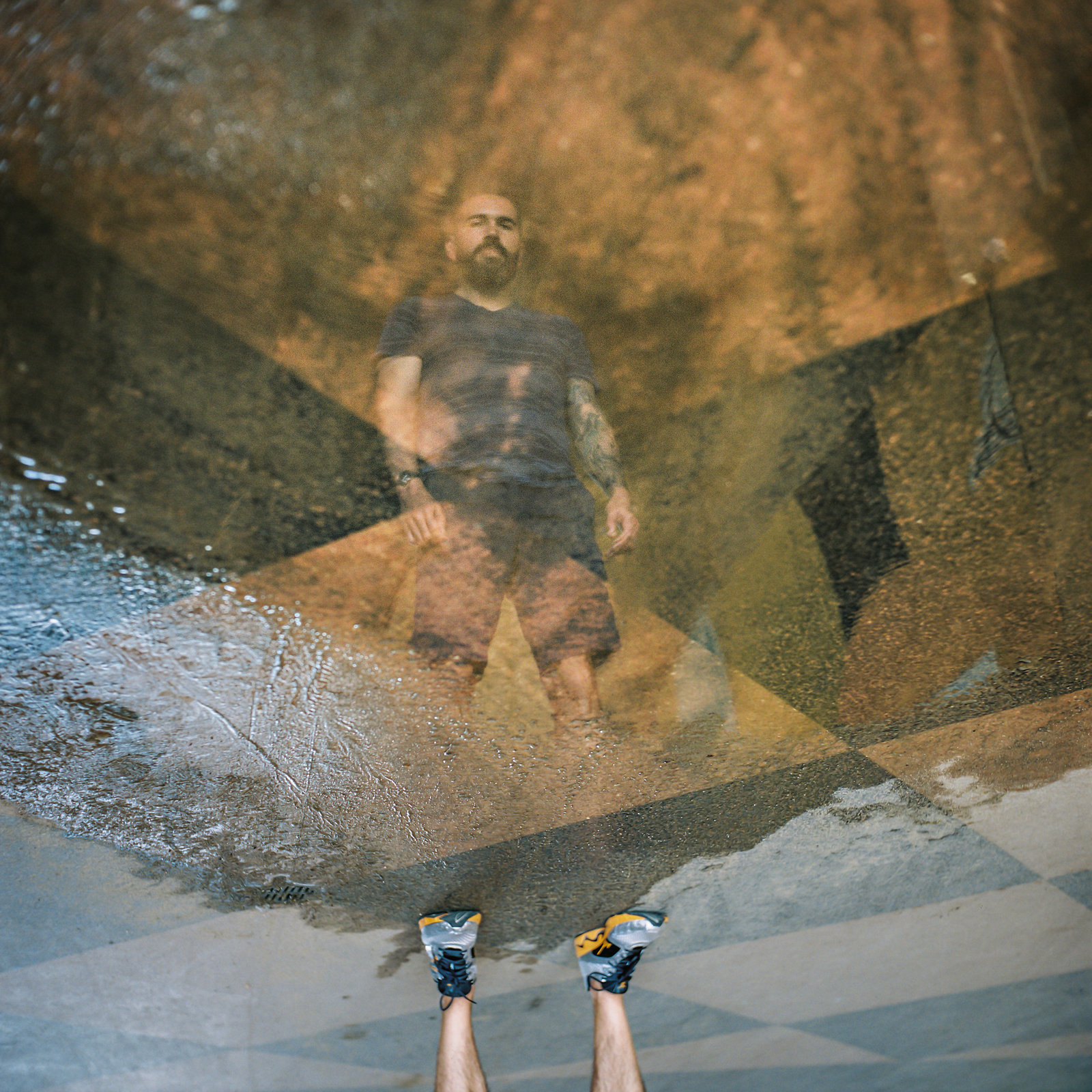 A reflection in standing water of a man upside down.