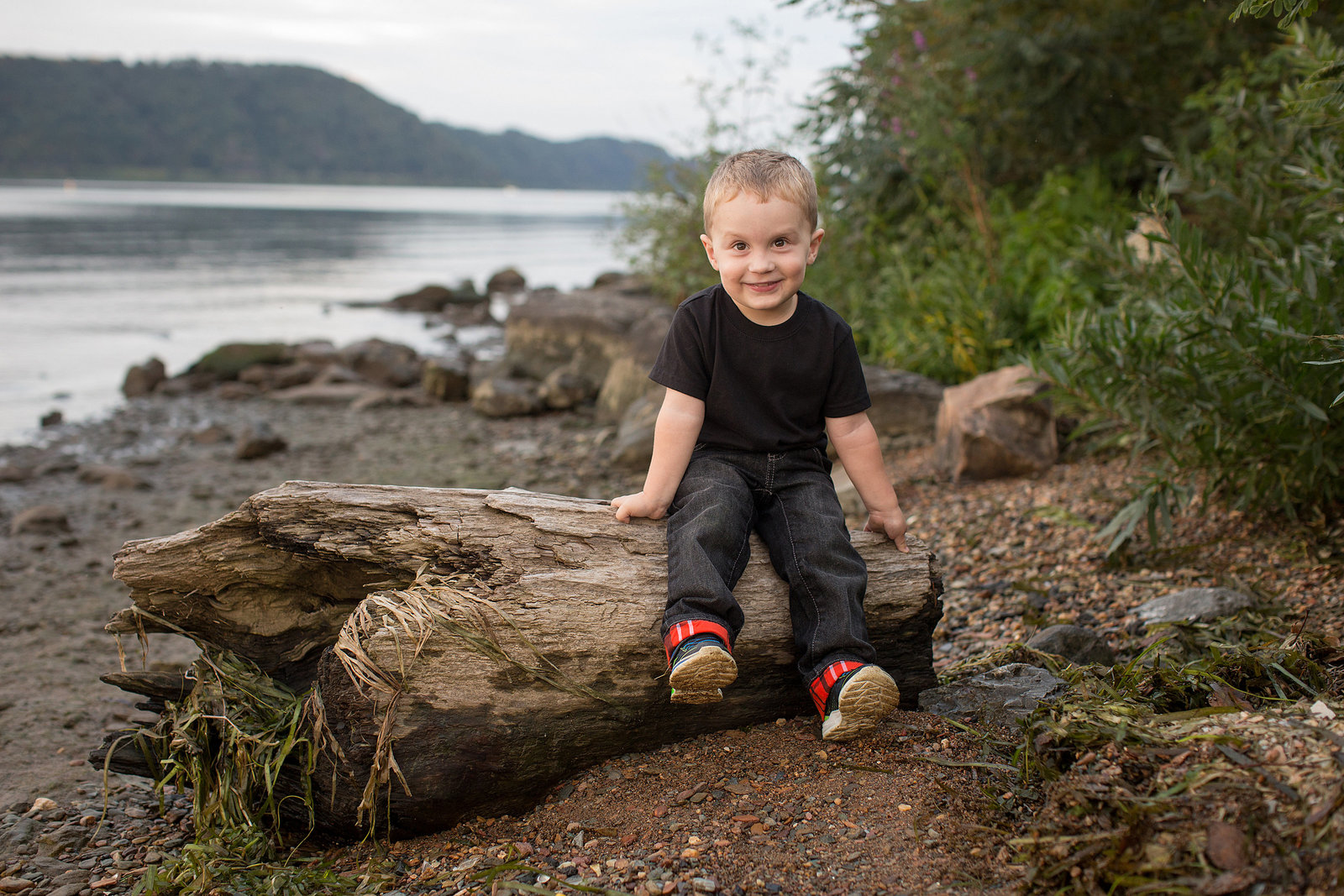 toddler sits on log  laughing