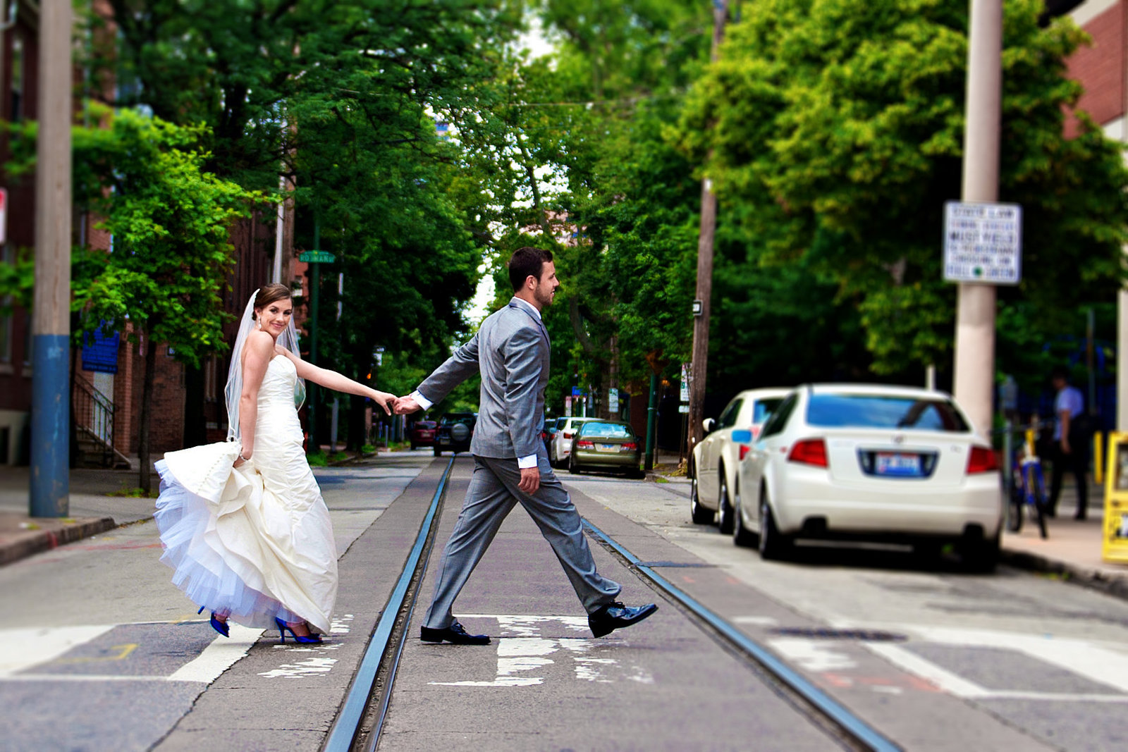 A groom leads his beautiful bride across South Street in Philadelphia