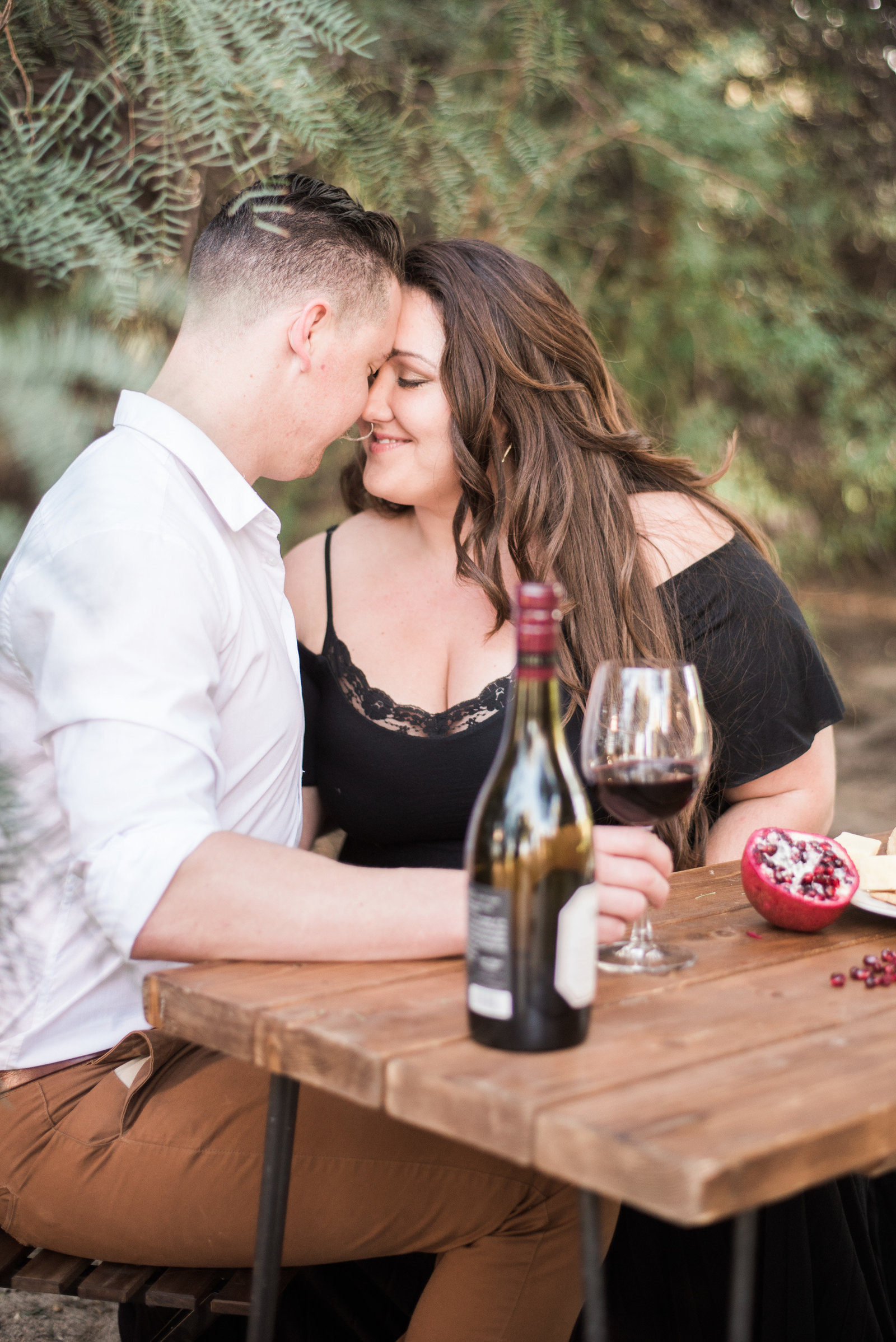 Romantic engagement session photo of couple during dinner and wine