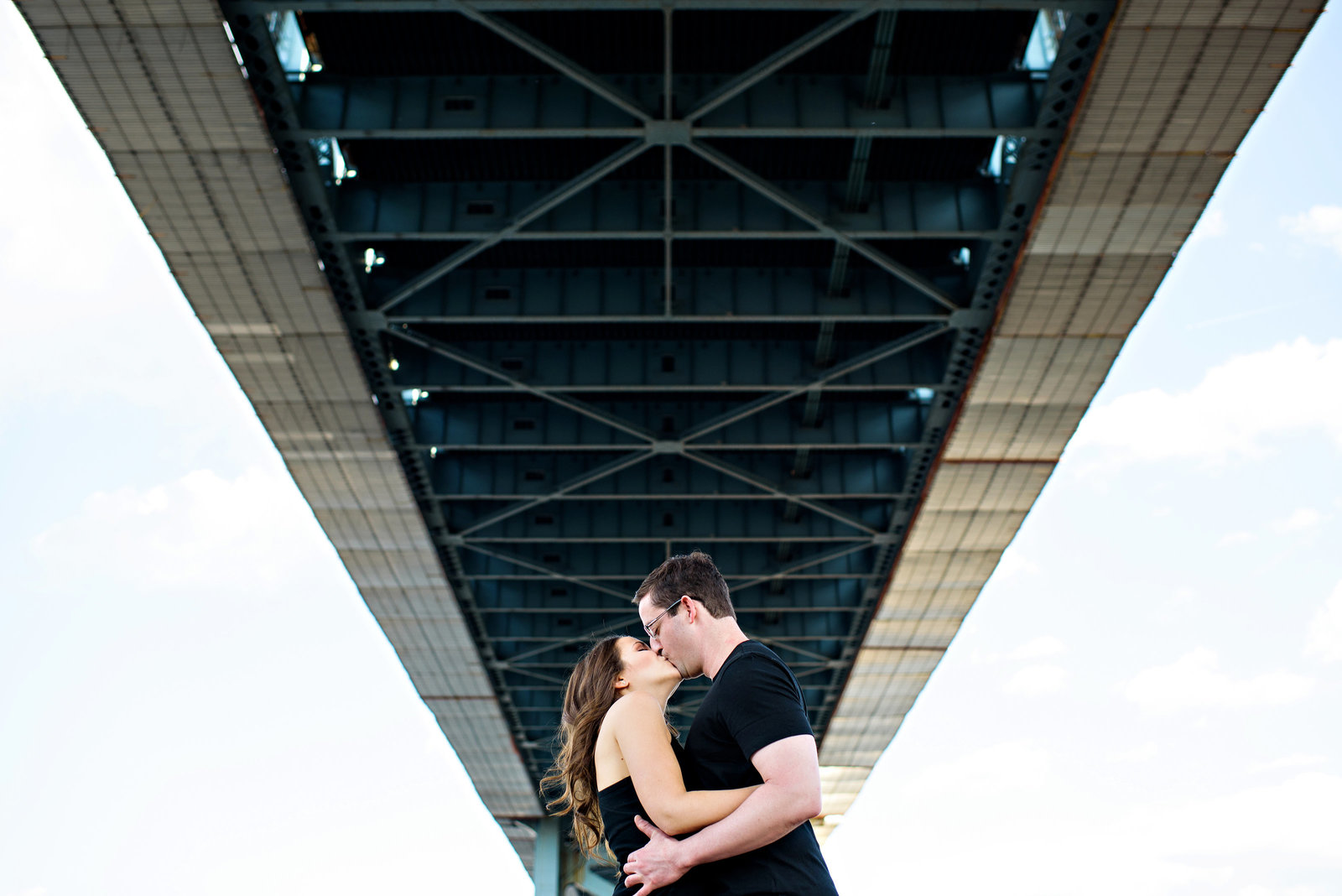 Two people in love kiss under the ben franklin bridge.