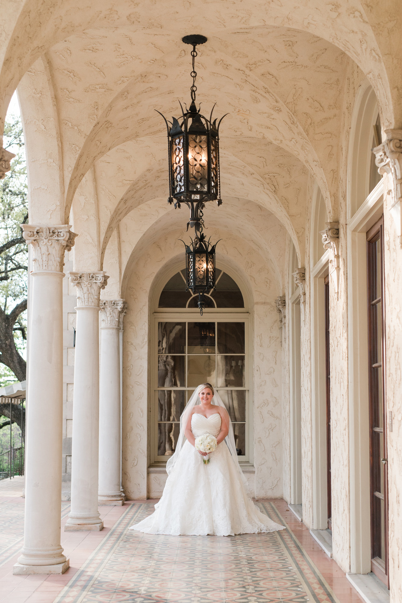 Bride stands on patio of Commodore Perry Estate for Bridal Portrait in downtown Austin, Texas