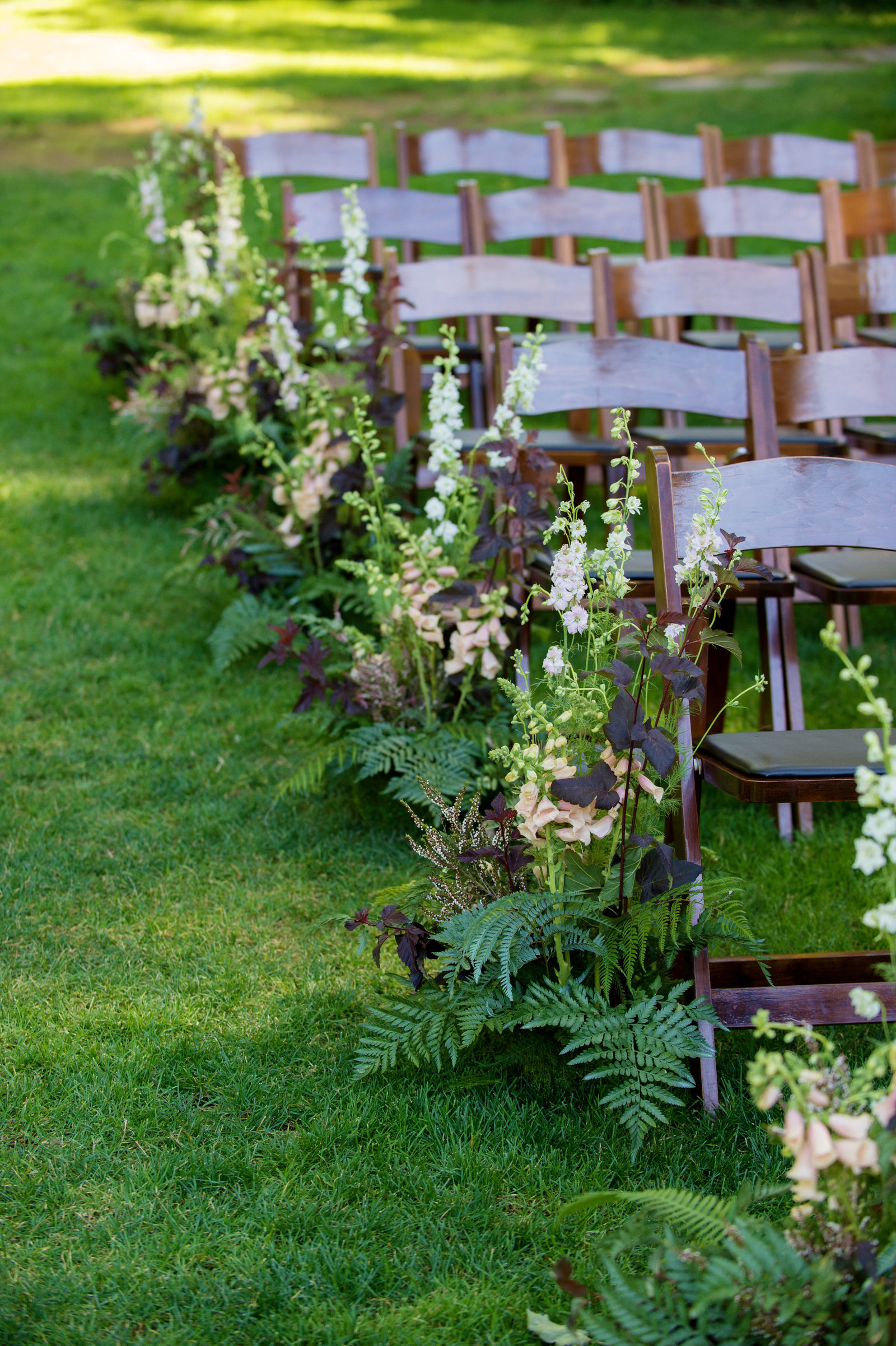 greenery and ferns decorate the wedding ceremony aisles outside