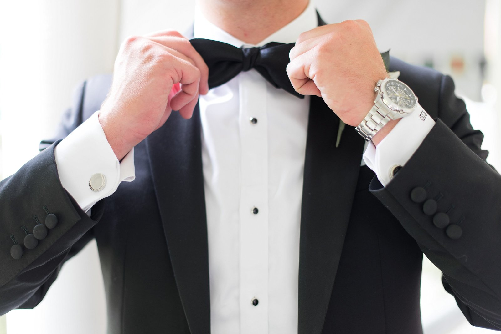 Classic Photo of Groom getting ready in a black tuxedo and fixing his bow tie