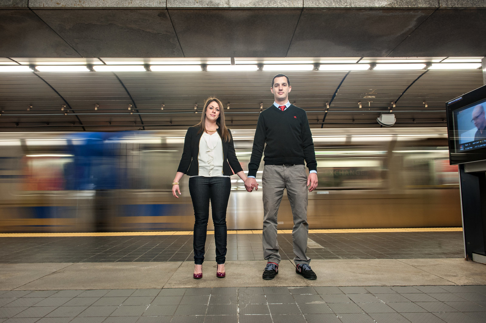 A couple hold hands in front of a moving nyc subway train.