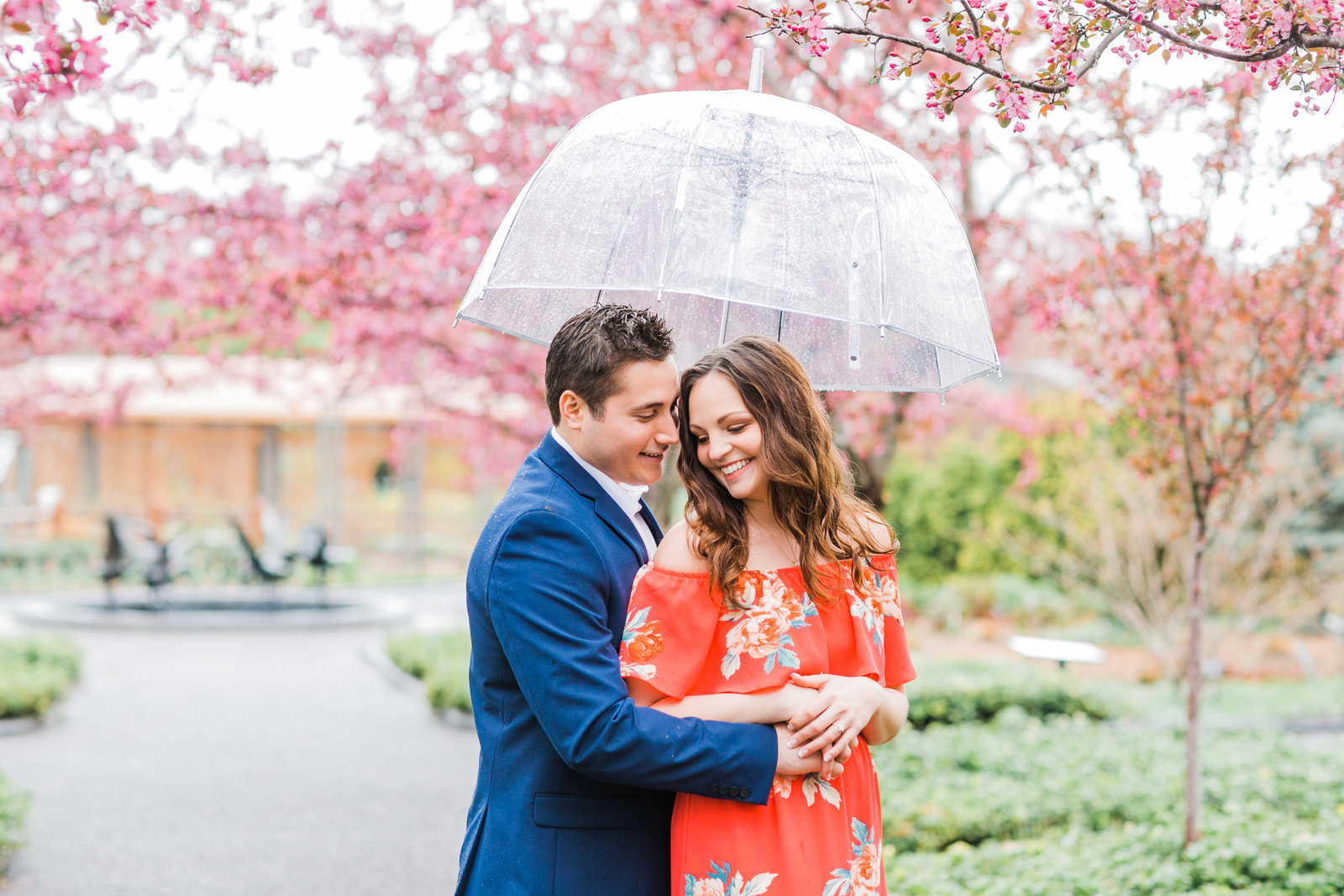 Ale hugging Suzie under a clear umbrella while Suzie laughs and they are standing in front of pink blooming crab apple trees