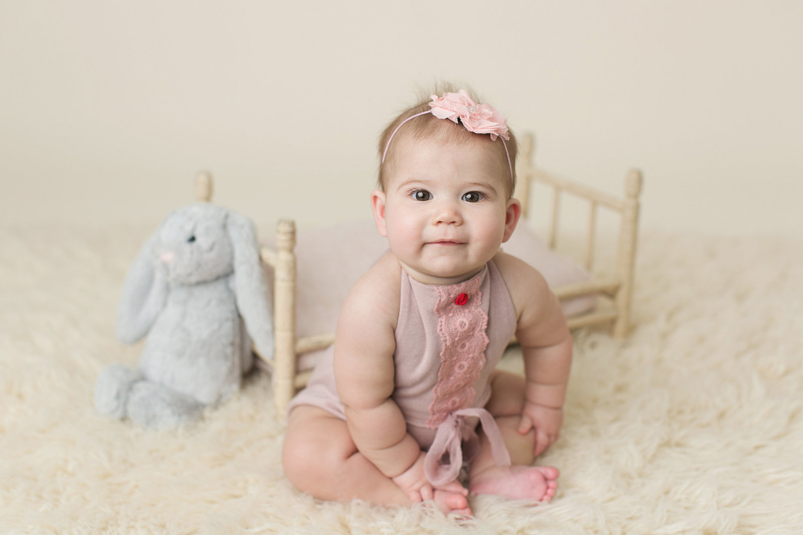chubby baby sits with stuffed toy