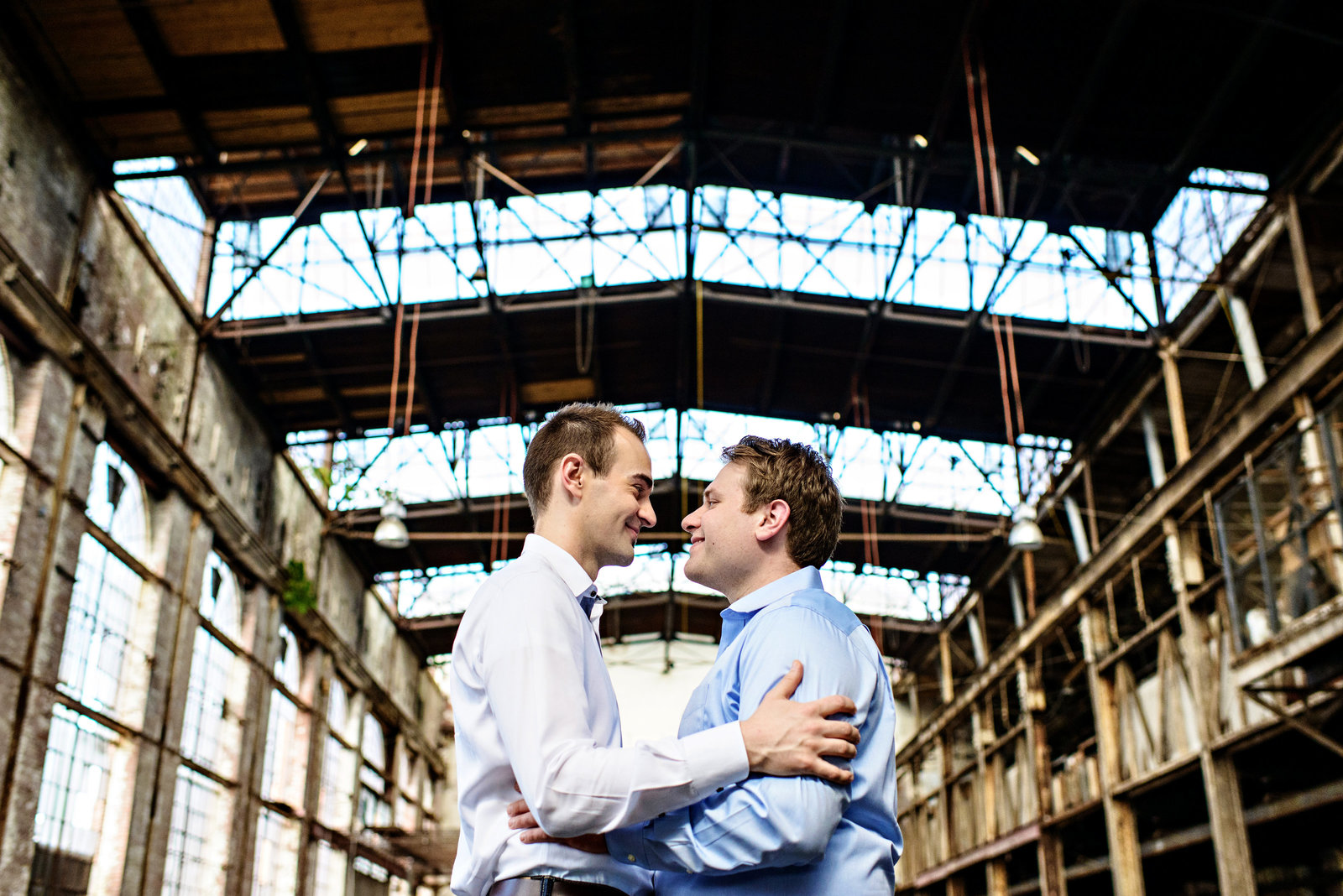 A same sex couple hug in an abandoned warehouse in baltimore, md.