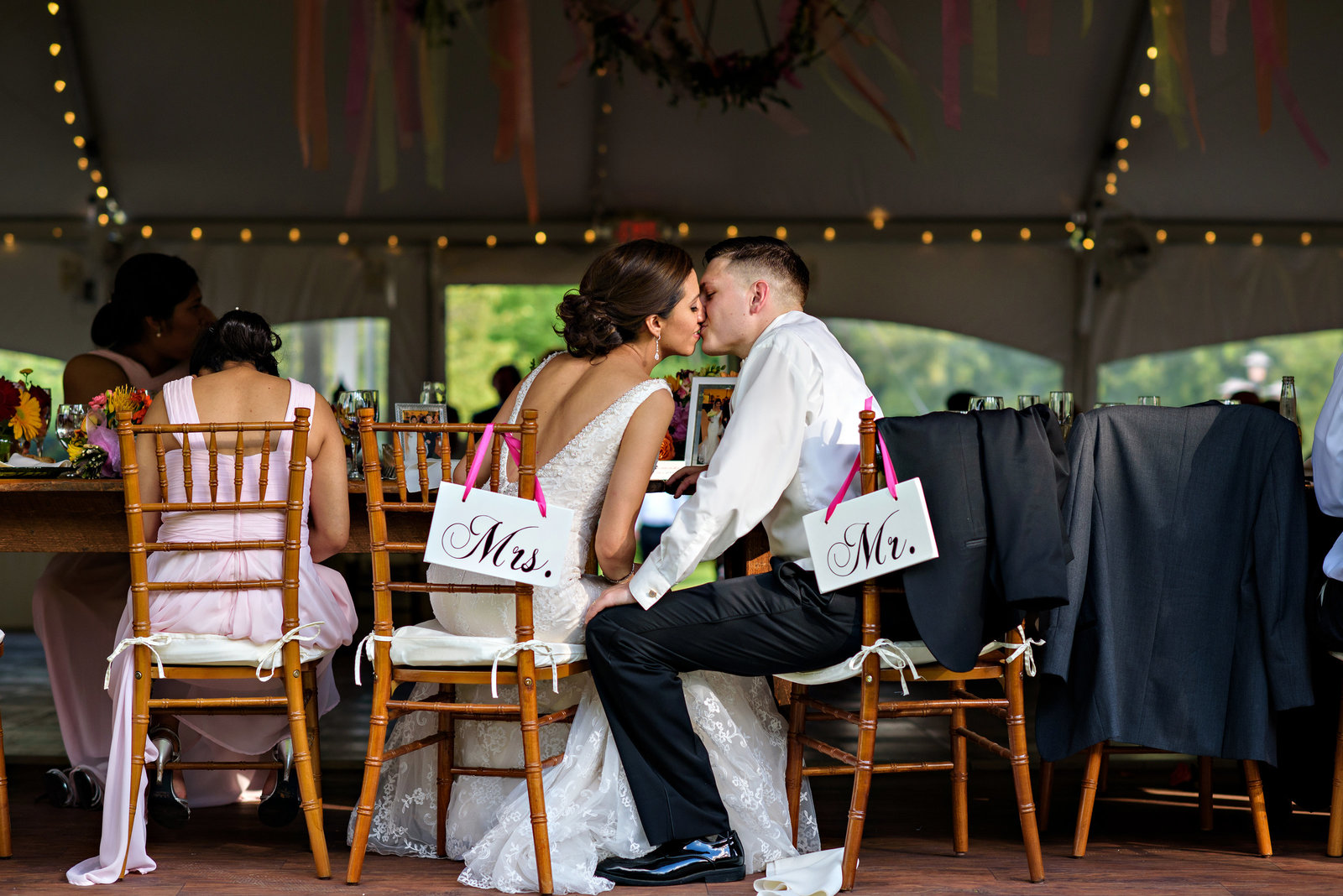 A bride and groom kiss at their wedding table during the reception at Pearl S Buck Estate.