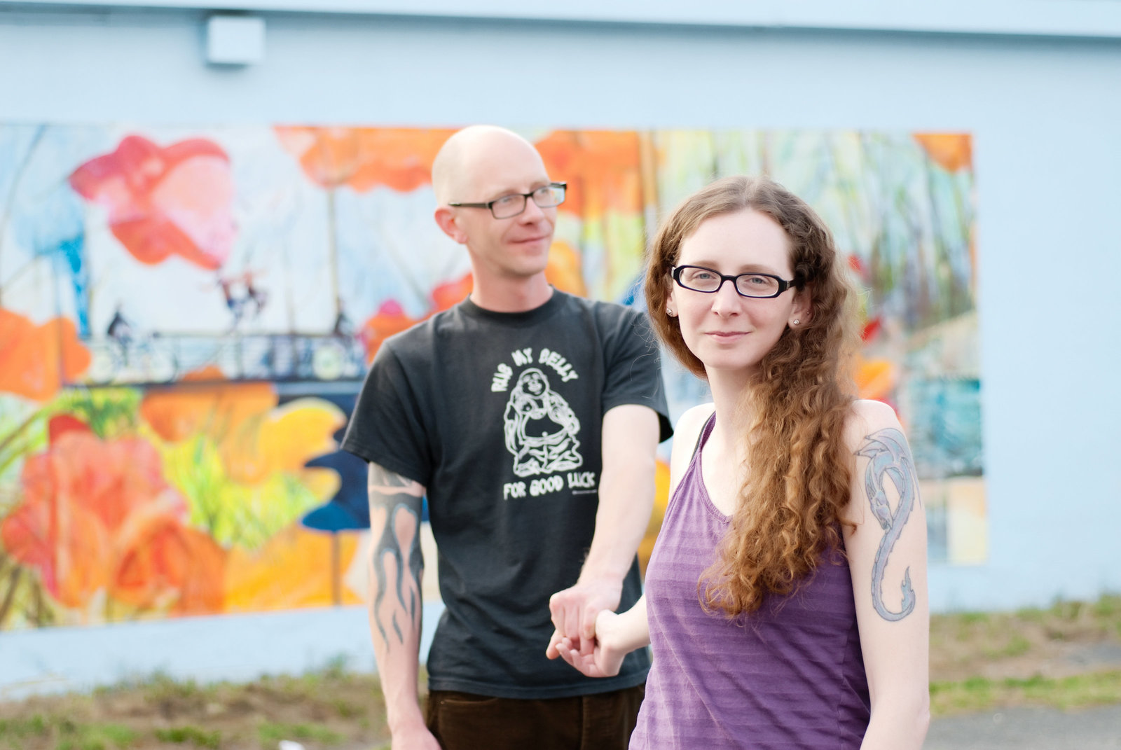 a couple stand in front of a colorful mural in charlotte