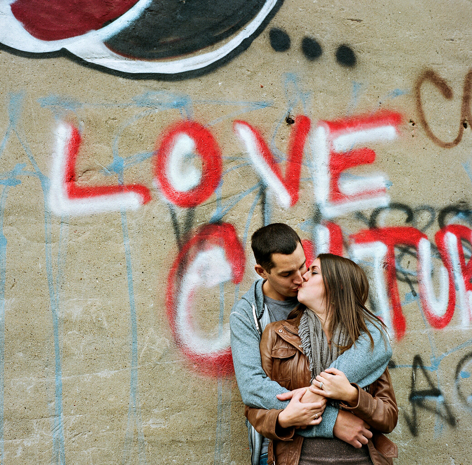 A couple kiss with the word love written on the wall behind them.