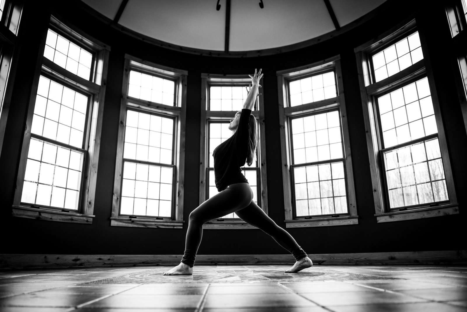 Black and white portrait of yoga instructor in Warrior 1 pose.