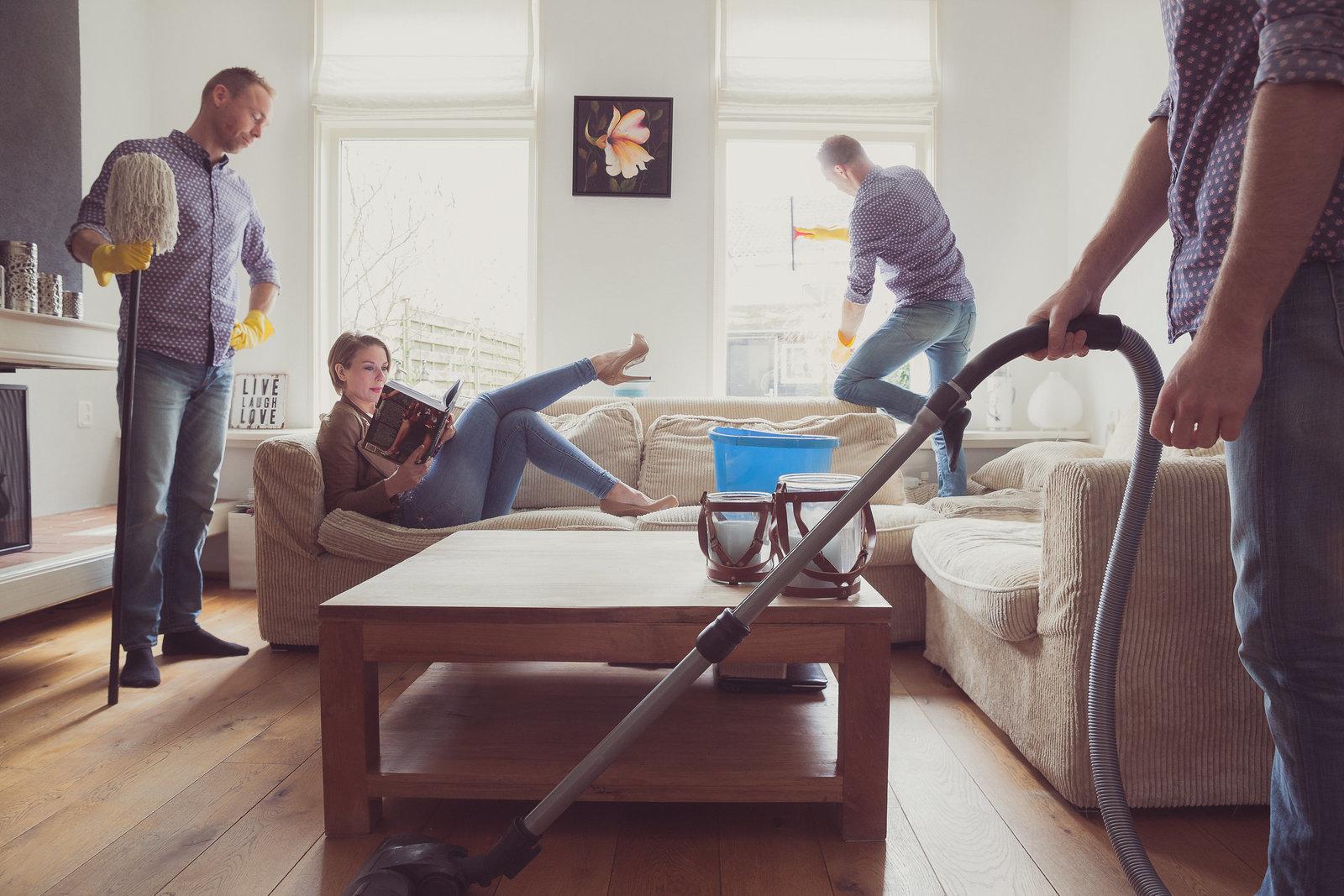 Hilarische foto van een koppel waarbij de huishoudelijke taken goed verdeeld zijn. Terwijl zij op de bank een boek leest, maakt hij het huis schoon. Copyright Nanda Zee-Fritse | FOTOZEE
