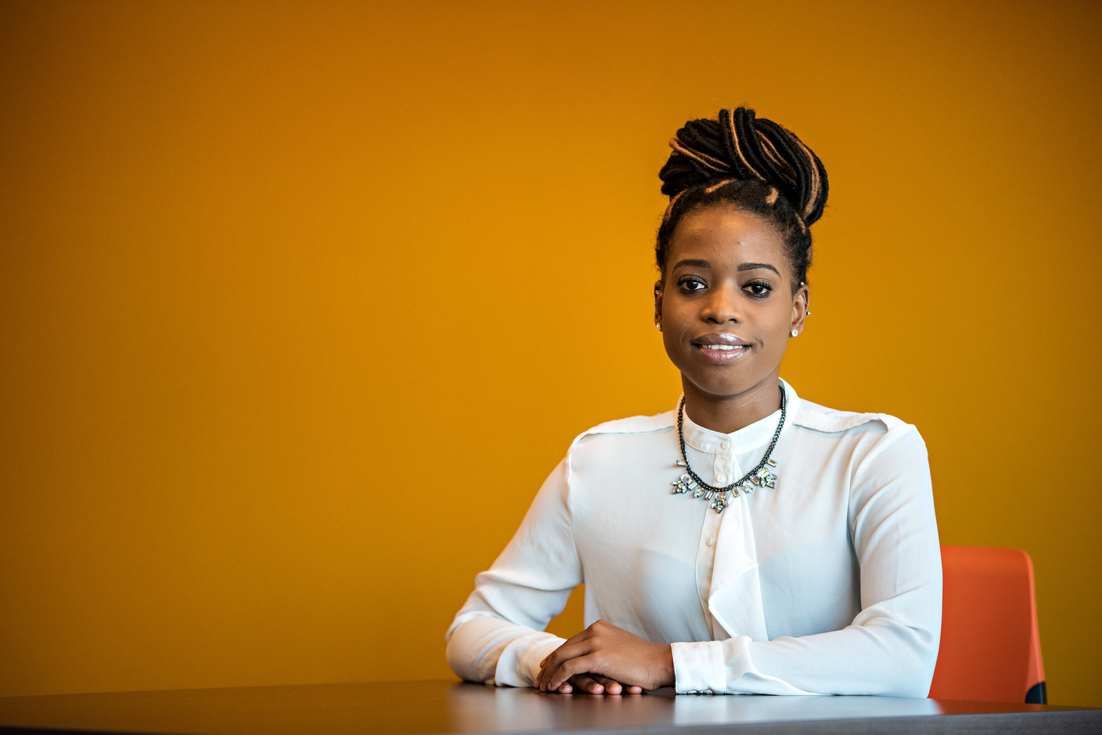 A young professional woman sits at a desk in front of an orange wall.
