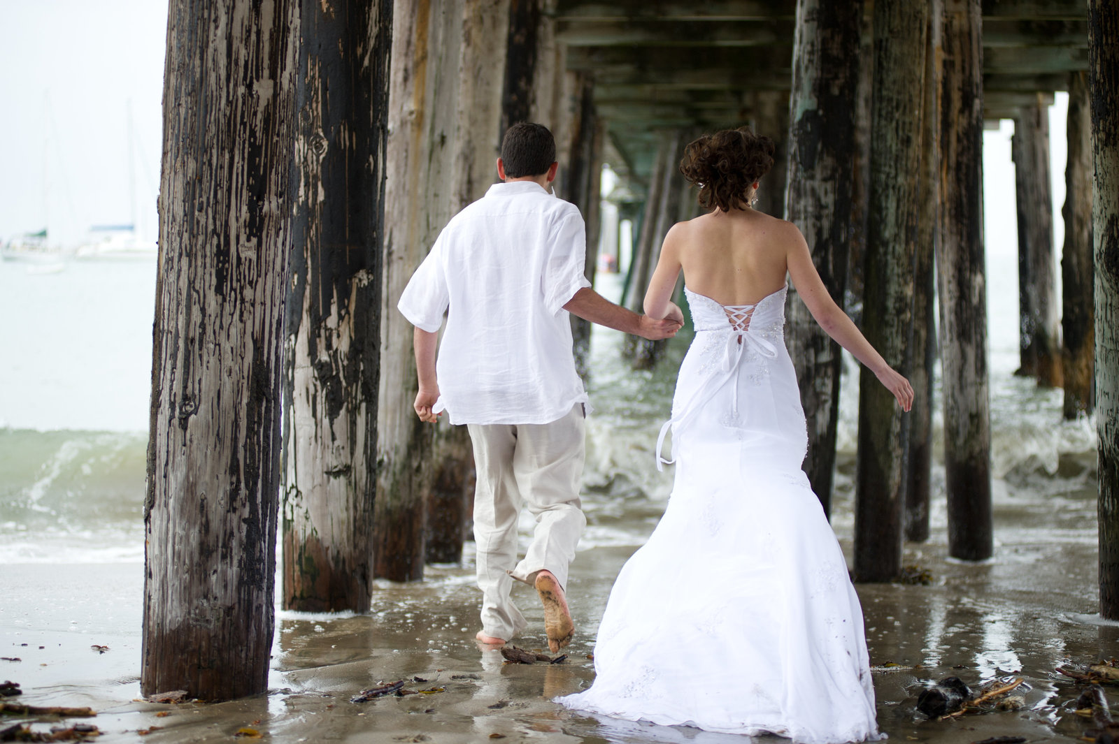 In beautiful beach engagement session, the couple walks under the pier in northern california