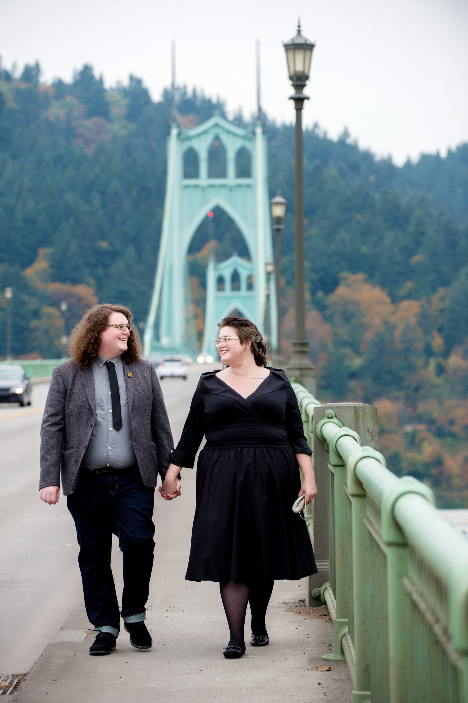 an engaged couple walk hand in hand with the st john's bridge in the background