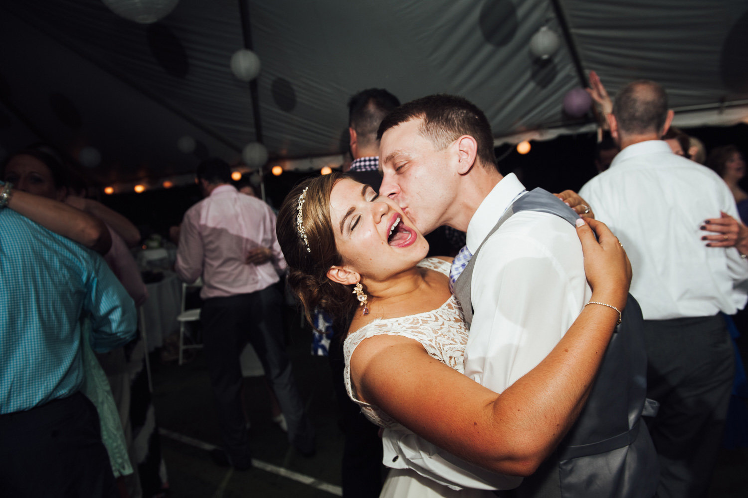 Bride and grooms kiss on the dance floor of a back yard, Philadelphia wedding.