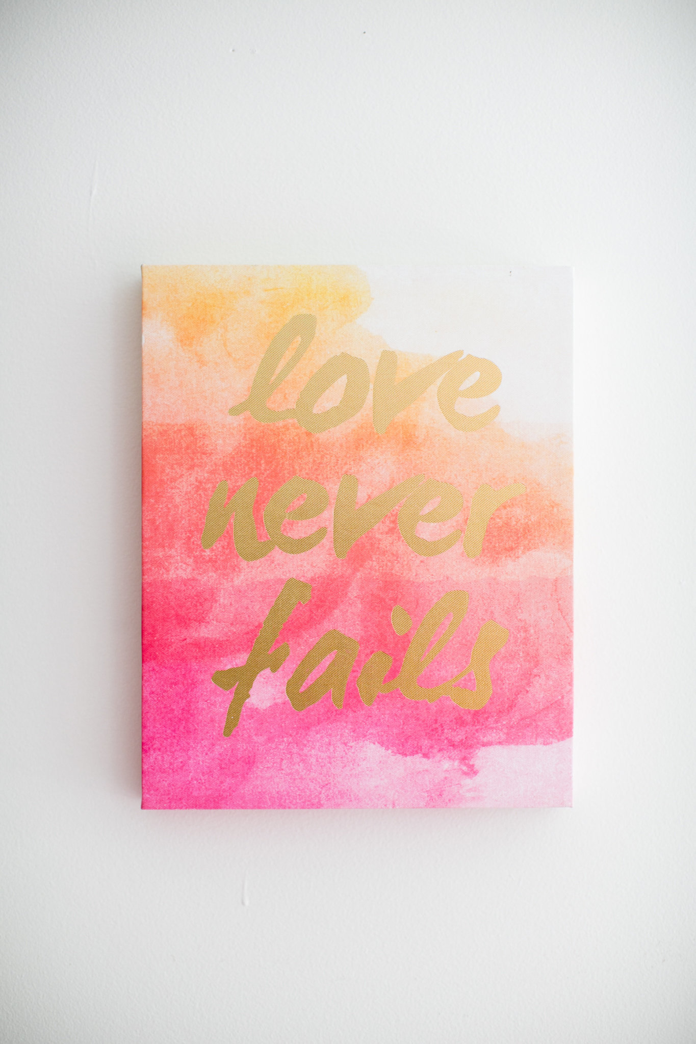 love never fails sign in gold lettering