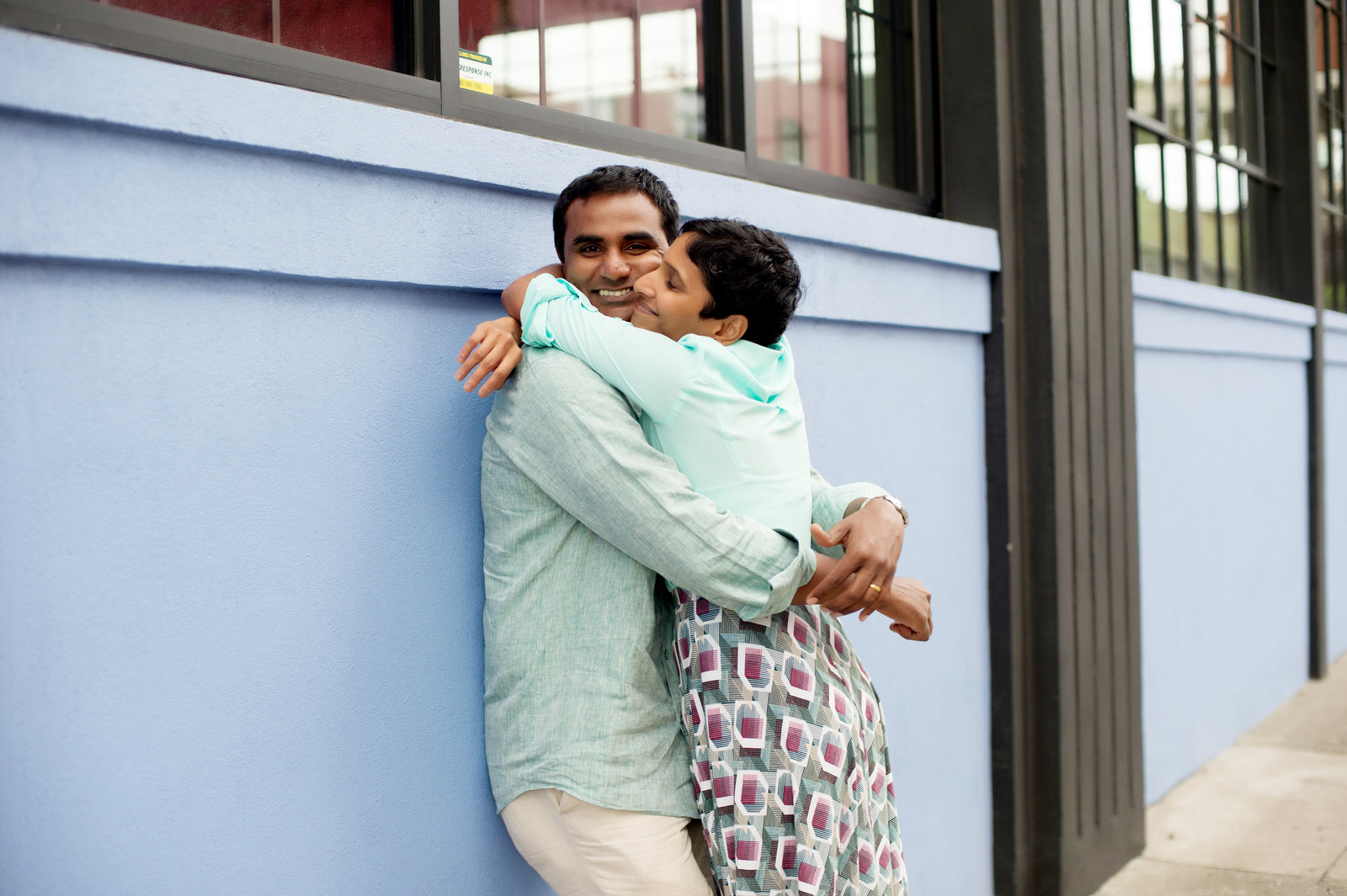a husband and wife embrace in front of a blue wall in nw portland