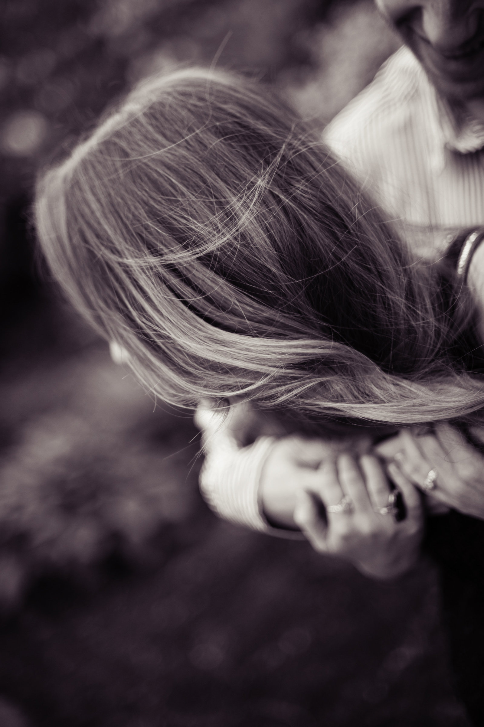 a girl's hair blows in the wind as her fiance hugs her from behind