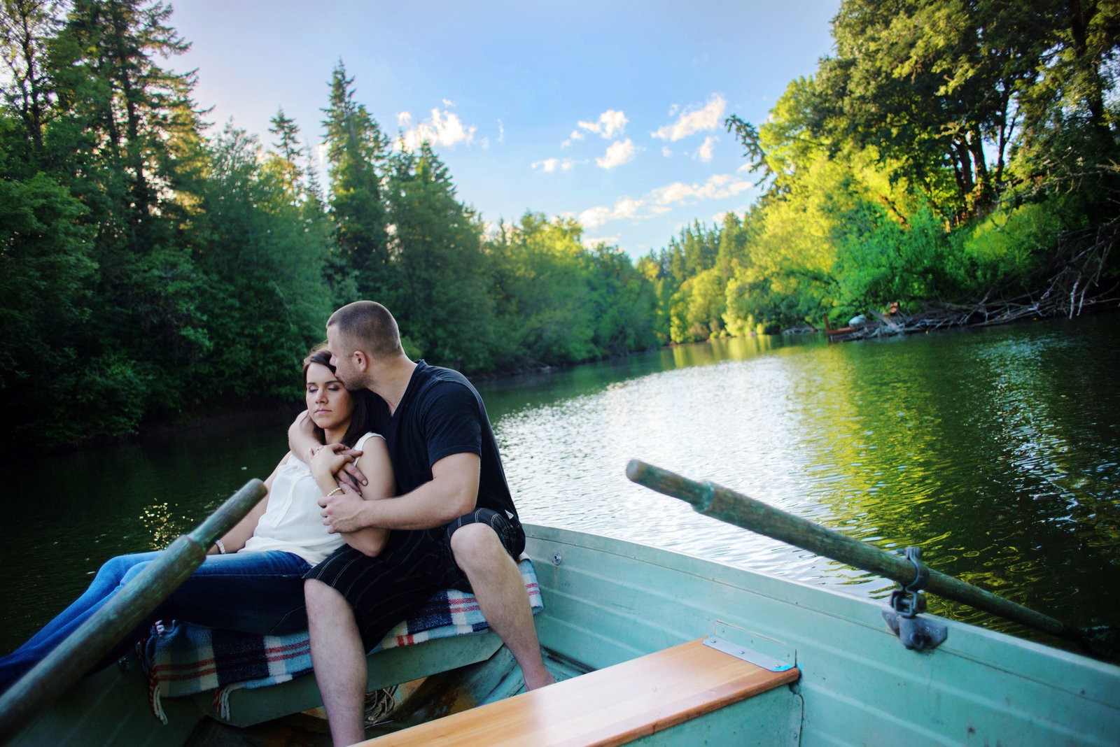 a couple embrace in a row boat on the clackamas river