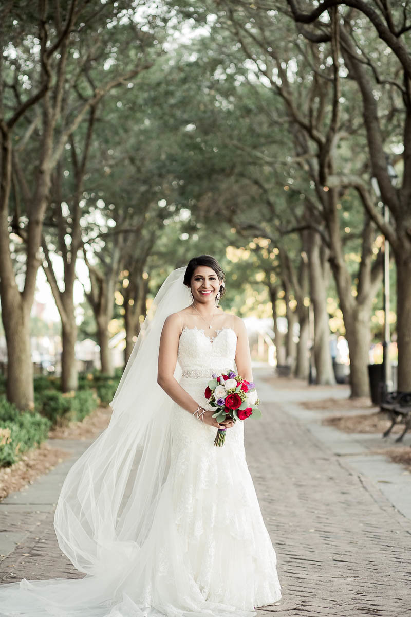 Bride stands under trees at the Waterfront Park, Charleston Wedding Photographer.
