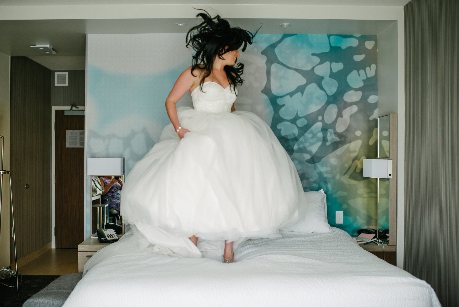 Youngstown OH bride jumping on bed in hotel room in her wedding dress
