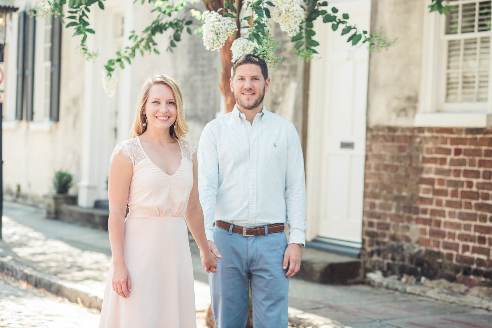 Engaged couple walks down a cobblestone road in the French Quarter, Downtown Charleston, South Carolina