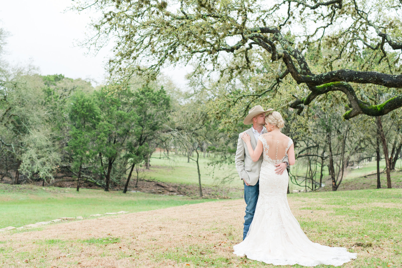Groom in jeans and cowboy hat kisses bride's forehead at Rustic Ranch